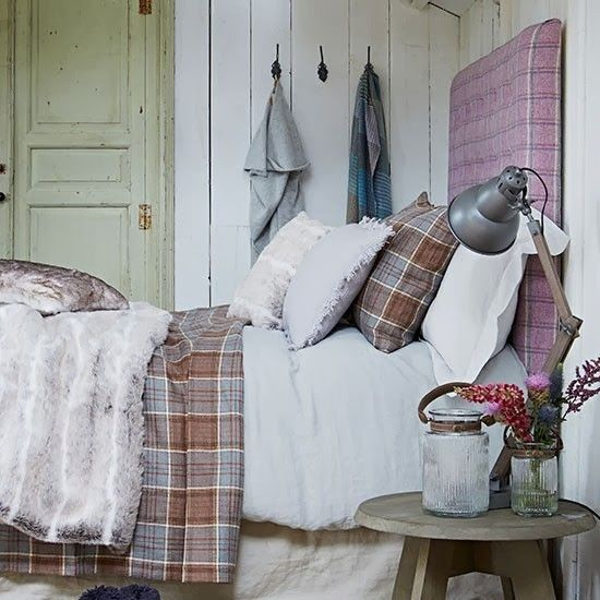 plaid headboard, plaid beddings, wood panels, old door, vintage jar, vintage stool as nightstand, some sort of fur on top.