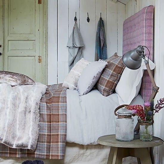 plaid headboard, plaid beddings, wood panels, old door, vintage jar, vintage stool as nightstand, some sort of fur on top.