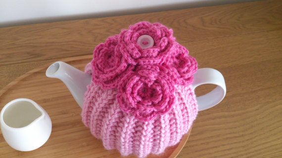 Pink hand knitted tea cosy with  crochet flowers and  button