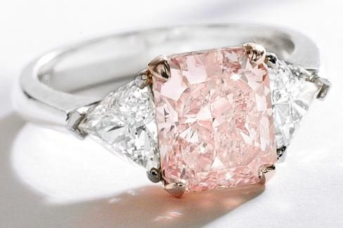 Pink diamond and diamond ring with a cut-cornered rectangular modified brilliant-cut fancy light pink diamond weighing 3.03 carats, which is flanked by two modified triangular-cut diamonds weighing approximately 1.00 carat. Via Diamonds in the Library.
