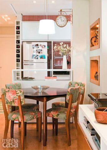 Ao redor da mesa redonda de madeira reúnem-se cadeiras de madeira maciça estofadas com uma charmosa estampa floral. Repare no relógio de parede e também na adega que guarda vinhos no espaço ao lado da geladeira. Projeto da arquiteta Cristiane Dilly.
