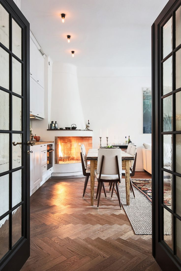 Herringbone wood floor, steel framed French doors, corner fireplace - monochromatic and earthy