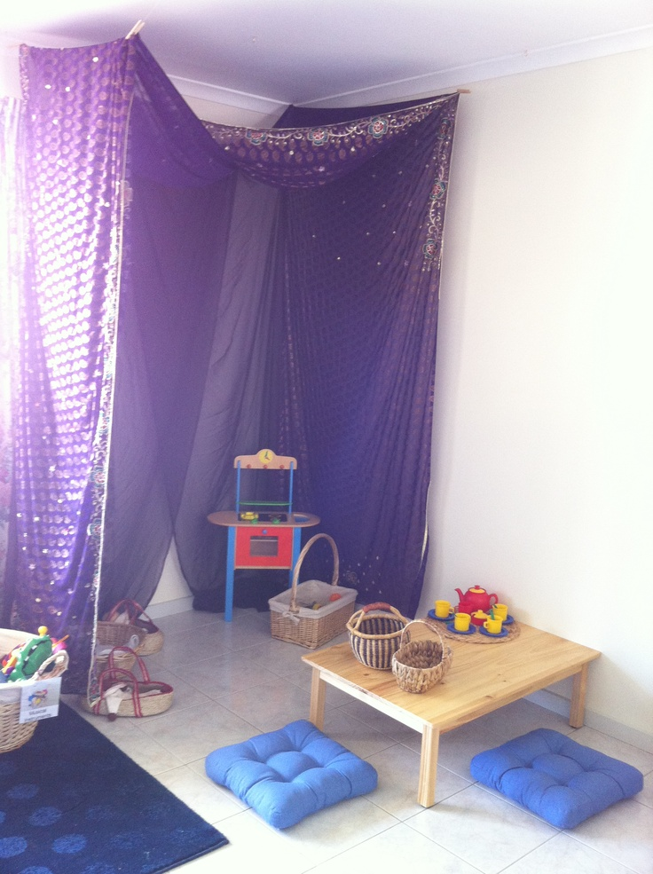 Home Corner - Aldi cooker, basket of play food and utensils, 3 dolls in baskets in left corner. Sari over the top and purple chiffon at the back, both draped over fishing line strung between hooks in the ceiling. Tea set on low table in front.