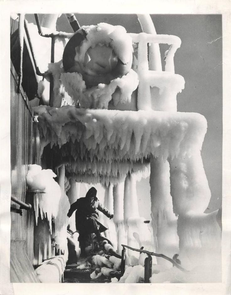 1944 - Sailor make his way across deck of a Royal Canadian Navy Corvette coming through a tour of convoy escort duty in the North Atlantic with a heavy coating of ice.