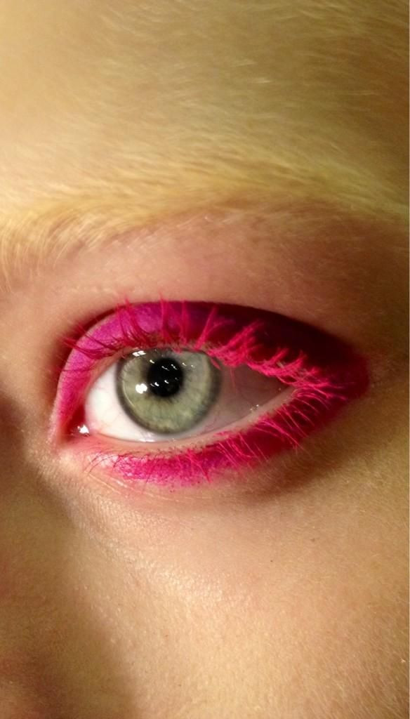 Her eye looks like a sea creature... Neon pink eyeshadow. No eyeliner no mascara. Guard makeup.
