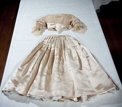 Queen Victoria's tiny wedding dress. All British-made fabrics used, and the pattern for the Honiton lace was destroyed afterwards to avoid copies. Decorated with orange blossoms on Victoria's big day!