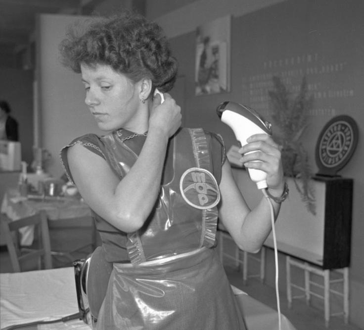 Na III. výstavě československého strojírenství v Brně v roce 1957 žena předvádí sušič vlasů.