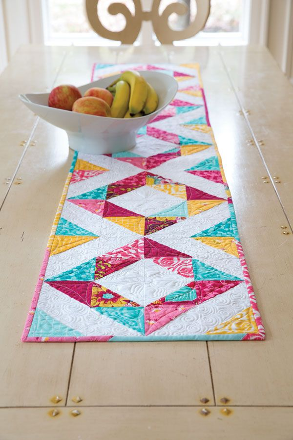 Designer Pam Biswas loves having a table runner for every season. This one is perfect to celebrate spring. Spring Table features half-square triangles arranged in a square-in-a-square fashion.