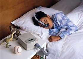 Boy using PAP device to treat sleep apnea.  Sleep Apnea does effect children too!