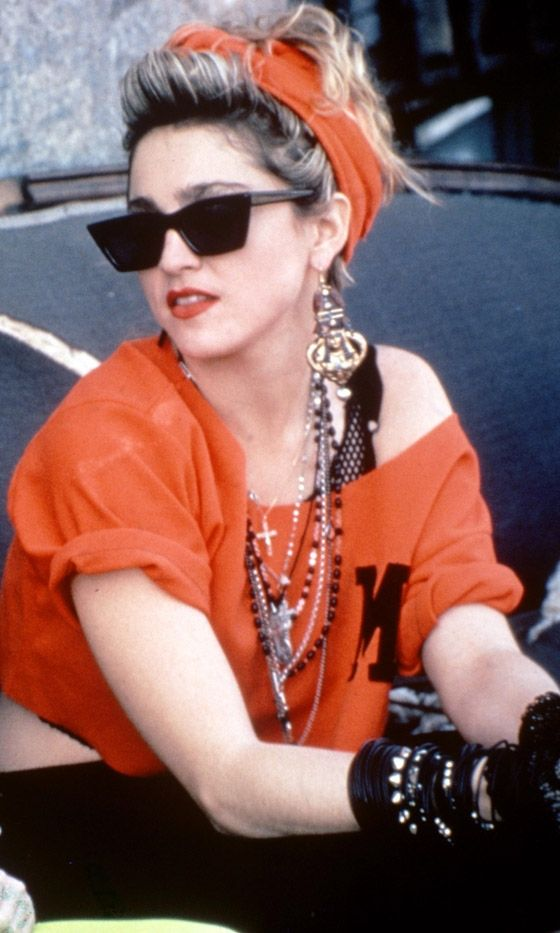 This 1980's look is an older style. A off the shoulder bright orange crop top with the same color orange as a headband, and some beads and christian looking necklace.
