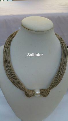 collier en fil de lin, agrémenté d'une grosse perle en métal et de petites perles en métal, tenu par 2 bagues