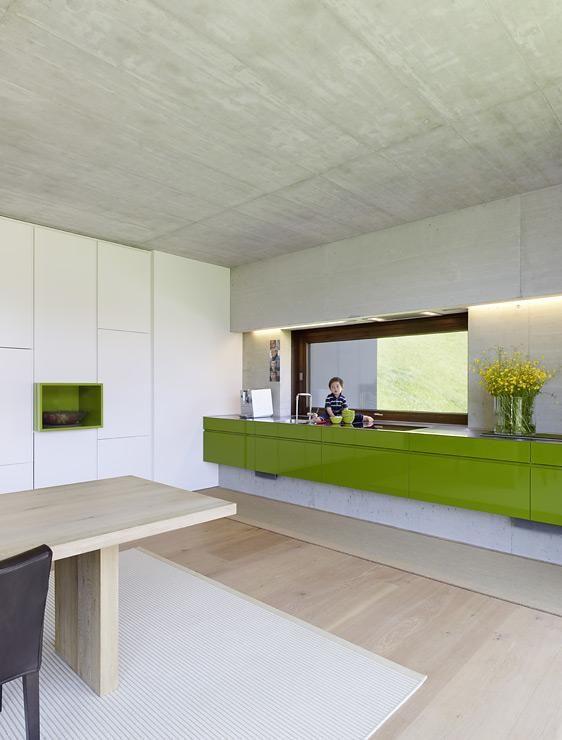 Grüne Küche mit Sichtbeton, interessanter Fensterumbau mit Licht und Dundtabzugshaube