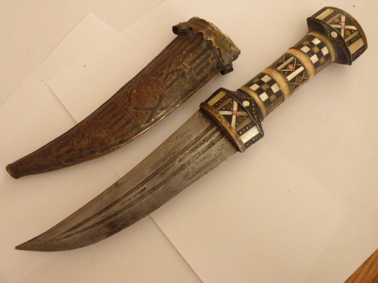 "Janbia, dating from mid 1800's with an inscription in arabic ""khedive of Egypt"" on the back unknown if that is previous owner o name of knife, handle is inset with coral, mother of pearl, brass,bone (or ivory),brass pins.  A considerable amount of work as well as a unique blade style whereas most of these knives were made with a raised center ridge, this blade has three grooves.  Sheath is made of wood covered with brass ...."