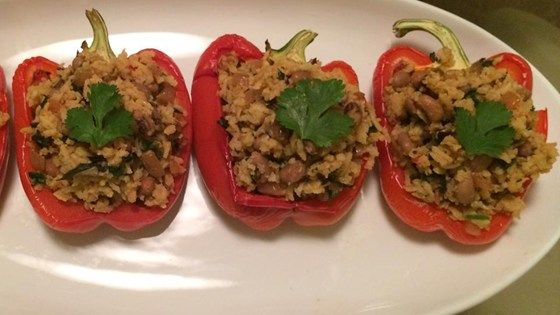Red bell peppers are baked, then stuffed with brown rice, chard, and black-eyed peas.