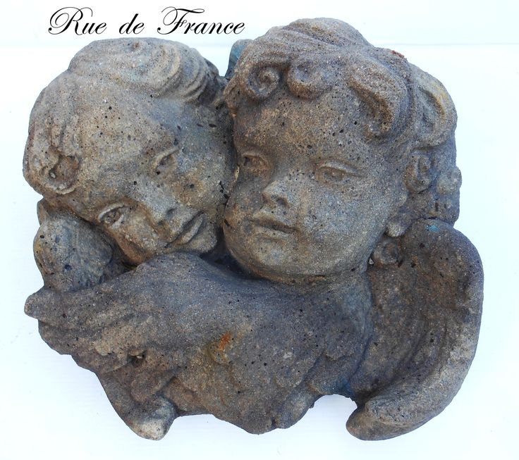 Cast stone wall plaque of twin cherubs