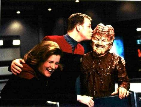 "Captain Janeway (Kate Mulgrew) and Tom Paris (Robert Duncan McNeill) having a laugh with a ""Hirogen hunter""."