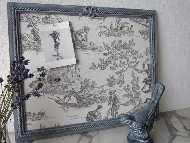 Cadre photos aimanté. Cadre en bois gris patiné. Fond recouvert d'un tissu motif toile de Jouy. Dimensions :  56 x 46 cm.