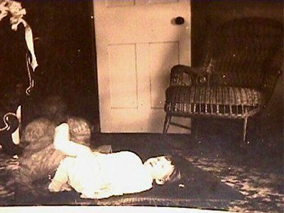 This is a real photo showing a child playing on the floor with what looks like a ghost right next to her legs. The ghostly image looks like a little girl in a puffy dress. There were means to fake photos in the early 1900s (I have seen faked photos), but this looks real to me. You decide.