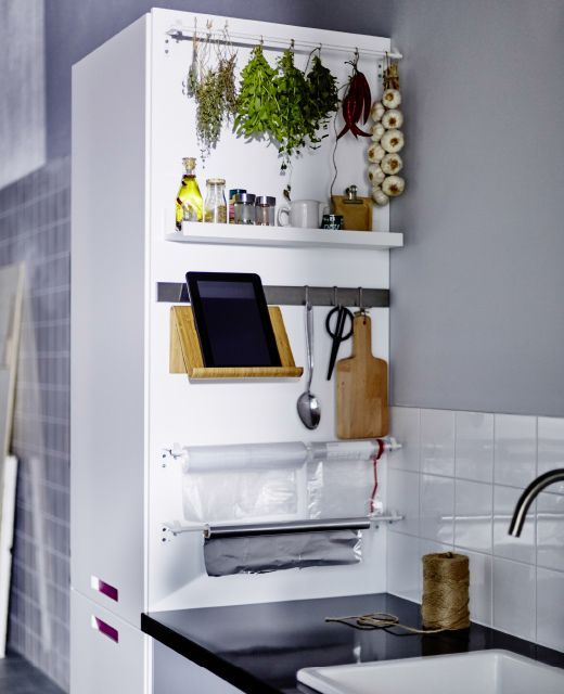 The side of a tall kitchen cabinet with baskets and rails for a laundry station