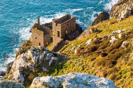BOTALLACK, CORNWALL, ENGLAND:   Tin mining played a significant role in the economy of Cornwall. While the tin mines may be shut down now, the abandoned houses offer visitors a chance to look back at the region's historic past, set against the dramatic backdrop of Cornwall's rugged coastline.  Ian Woolcock/Getty Images