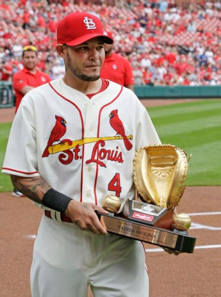 catcher Yadier Molina receives his Rawlings Gold Glove award for his play in the 2014 season before a game against the Cincinnati Reds. 4-18-15