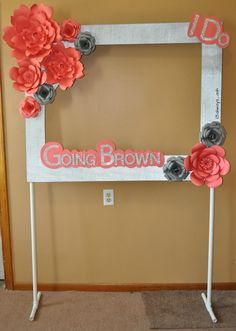 Photo booth frame with paper flowers on a pvc pipe stand
