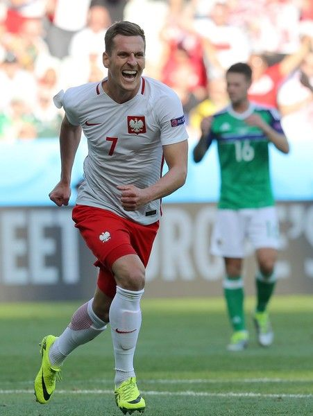 Poland's forward Arkadiusz Milik runs in celebration after scoring during the…