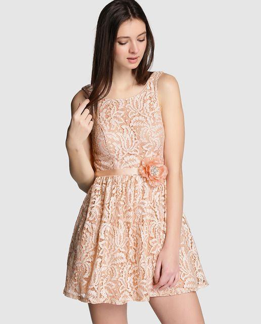 Vestido corto de encaje en color melocotón. Lleva adorno de flor con strass en la cintura y escote redondo.