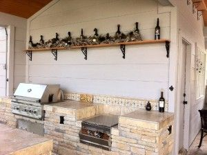 Closeup of a rustic outdoor bar and grill area designed and built by Outdoor Homescapes of Houston. It features a wet bar, RCS grill and dou...