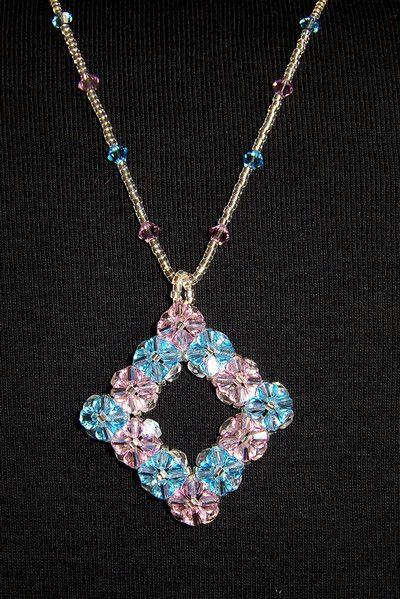 Colgante Primavera - Dos colores de tupis de cristal Swarovski formando flores, con base de facetadas de cristal checo y cordón confeccionado con los mismos tupis y delicas Miyuki de cristal plateado.