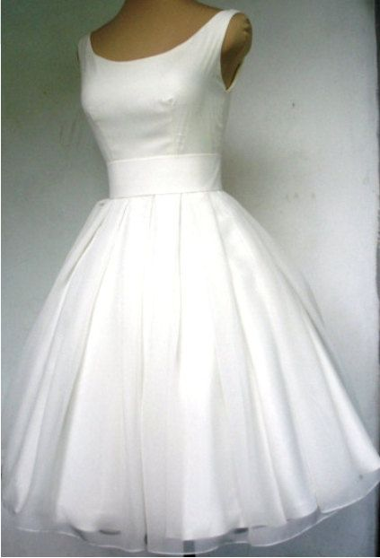 A beautiful ivory dress with a boat neckline. Made from chiffon with a darling tea length skirt which is pleated.