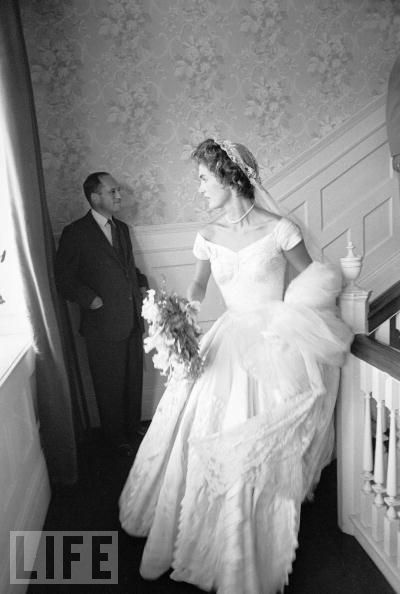 Socialite Jacqueline Bouvier waits on the landing of a staircase at her childhood home in Newport, R.I., the site of the reception after her 1953 wedding to Senator John F. Kennedy.