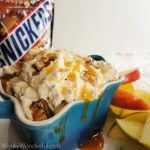 Creamy Snickers Dip:  Easy to make with only five ingredients .  This creamy dip with chunks of Snickers candy and a caramel drizzle that is perfect for parties or holiday gatherings.  You will want to eat this by the spoonful!  #dessert