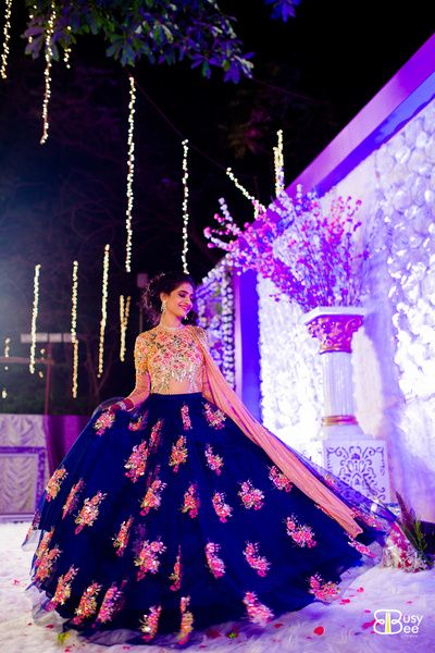 Sangeet Lehengas - Indigo Blue Lehenga | WedMeGood | Net Indigo Fairytale Lehenga with Pink Bootie Embroidery, Pink and GOld Embroidered Blouse #wedmegood #twirlingbride #blue #pink #net #indianbride #indianwedding #sangeetlehenga #lehenga