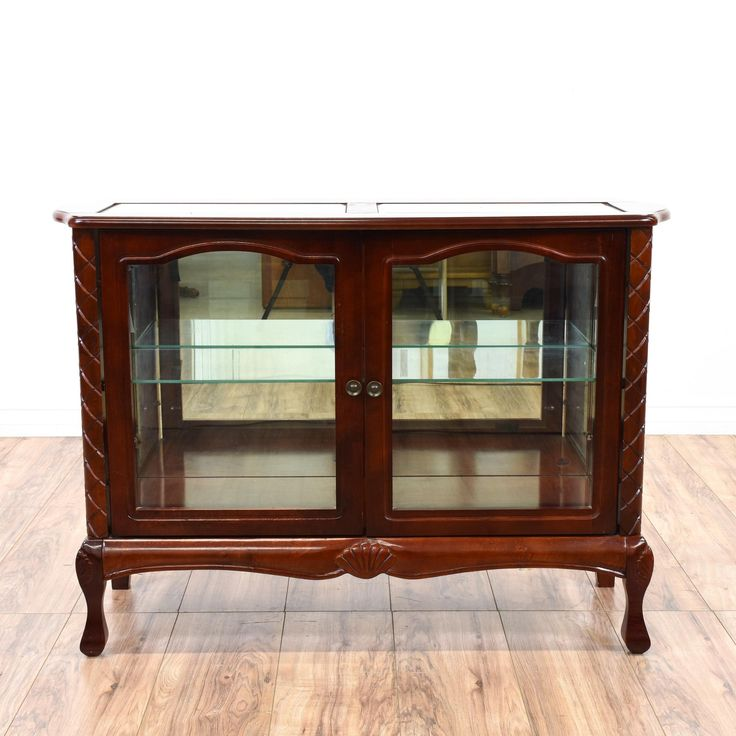 This low display case is featured in a solid wood with a glossy dark cherry finish. This display cabinet has a mirror back, glass accents and intricate carved accents. Perfect as a liquor cabinet bar for drinks and dishes! #asian #storage #displaycabinet #sandiegovintage #vintagefurniture
