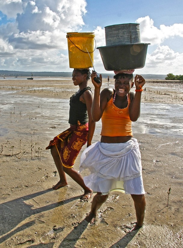 Girls breaking it down, transistor radio in hand with water buckets balanced on their heads, Mozambique, Africa.