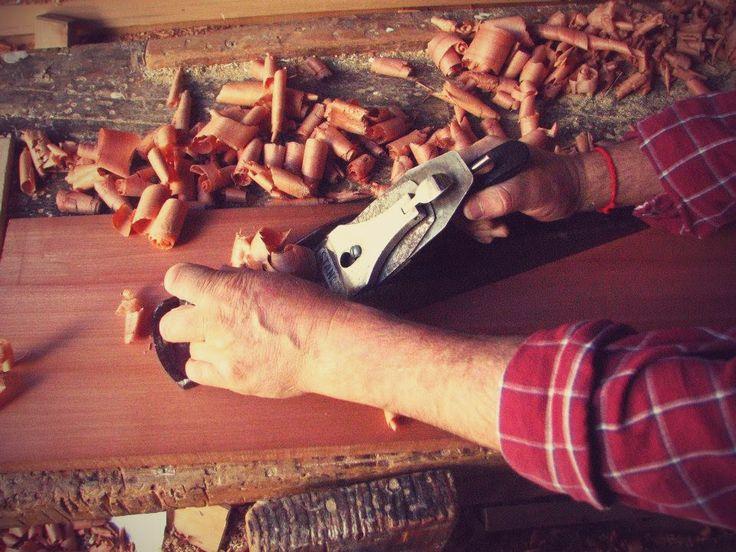 cepillando la madera para dejar  la superficie lisa y derecha.