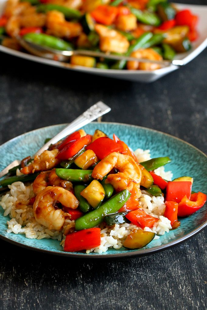 This shrimp stir fry recipe can be whipped up in minutes, is packed with veggies and served on a bed of aromatic jasmine rice.