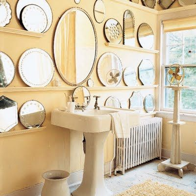 Dress up a cozier water closet with a wall of antique mirrors in different shapes and sizes for striking bathroom design- perched on several shelves, they act like lighting fixtures when reflecting the adjacent outdoor sunshine.