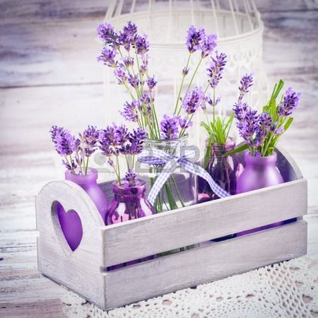 Lavender in bottles, decor provance style, wooden box and birdcage on crochet tablecloth Stock Photo