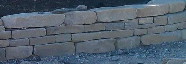 Base stone preparation is similar to wall site preparation being the foundation of your work. A dry stack stone wall has to have some of the largest and most stable stones here at the bottom.