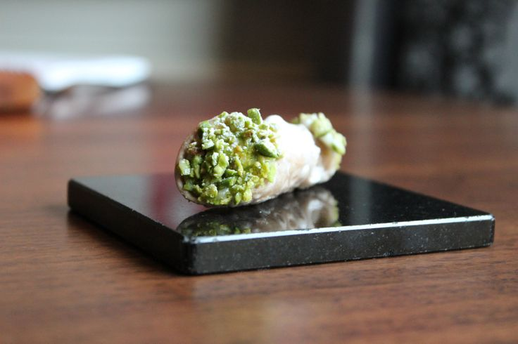 Sicilian Cannoli filled with ricotta cream and chocolate chips, crushed pistachio