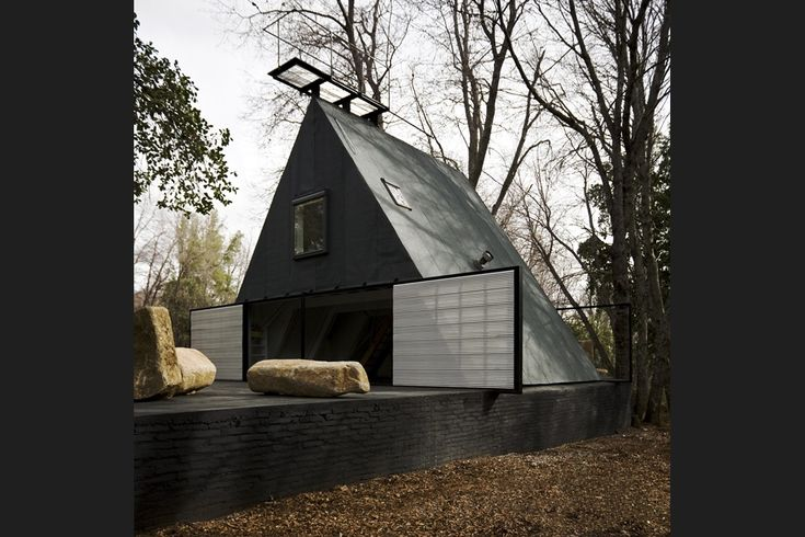 With its starkly simple form and dark materials, the renovated house has a brooding presence in the forest