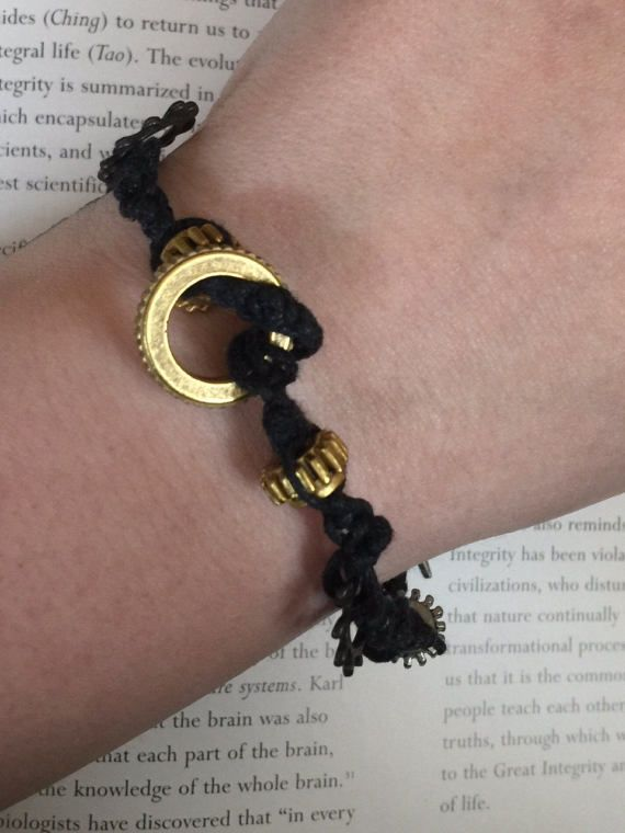 Charms are cogs and gears in antique metal coloring woven in waxed cotton cording by half knot. Closure is a makeshift toggle clasp comprised of two charms. Size: Large.