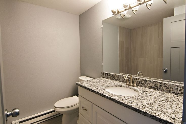 7019 Blacktooth Ave Gillette, WY has fully remodeled bathrooms - do you like these grey, tile & granite finishes? Call Team Properties Group for your showing 307.685.8177