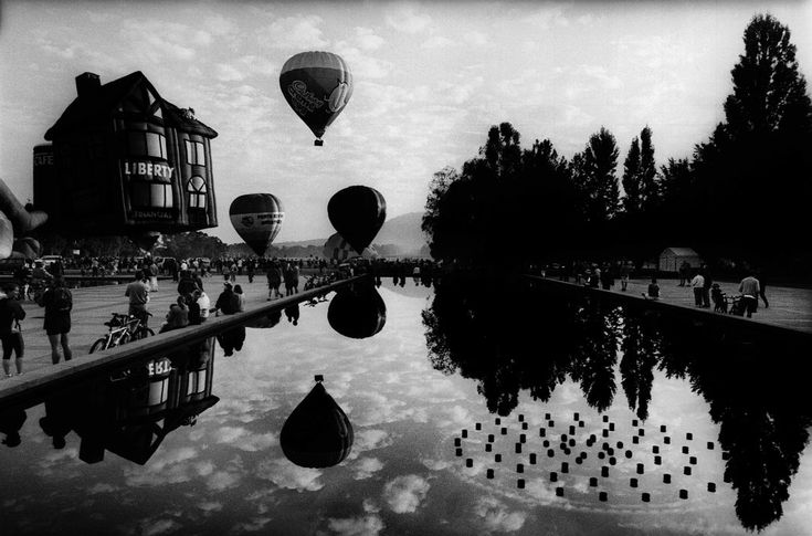 Trent Parke. AUSTRALIA. Canberra. Hot air balloons rise at dawn in front of old Parliament House during the Canberra hot air Balloon festival. 2003