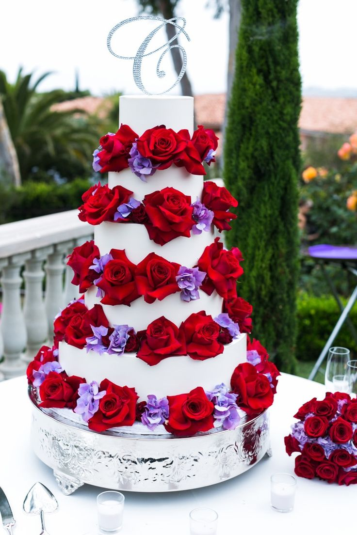 """This striking cake features red roses, purple flowers, and a sparkling """"C"""" topper. #InsideWeddings #WeddingCake Photography: Erik Umphery   Read More:  http://www.insideweddings.com/weddings/a-radiant-orchid-malibu-wedding-with-an-ocean-view/604/"""