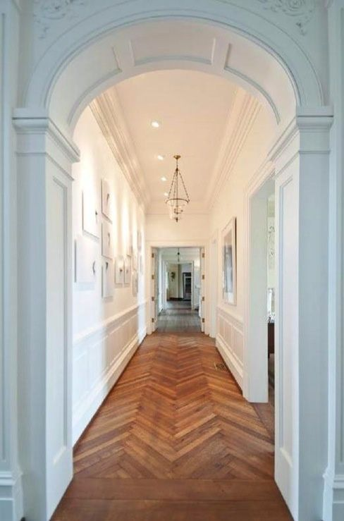 Stunning foyer with herringbone patterned wood floors arched doorways, wainscoting, Hundi Glass pendant and photo gallery. - Krunkatecture