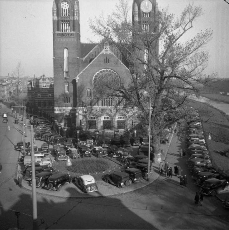 Parkeerdrukte voor de Koninginnekerk, rechts de Slachthuiskade en links de Boezemstraat, 1946. Op deze plek vind je nu woonzorgcentrum Hoppesteyn. Als herinnering aan de kerk is de bovenkant groen. De foto is gemaakt door de Dienst Gemeentewerken en komt uit het @stadsarchief010