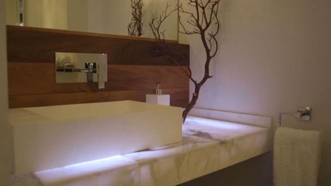 Cette salle d'eau compense l'absence de lumière du jour par un ravissant et chic éclairage artificiel. Le rétroéclairage du comptoir de quartzite donne un effet intéressant.